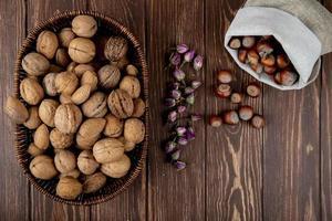 bovenaanzicht van hele walnoten in een rieten mand en hazelnoten verspreid uit een zak op houten achtergrond foto