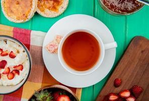 Bovenaanzicht van kopje thee met witte chocolade op theezakje en kom kwark met knäckebröd en perzikjam op groene achtergrond
