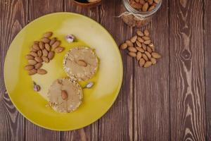 Bovenaanzicht van pindakaas met amandel op knapperige rijstcrackers op een gele keramische plaat met verspreide amandel op houten achtergrond