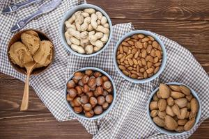 bovenaanzicht van gemengde nutsin shells in kommen pinda's hazelnoten amandelen op geruite tafelkleed foto