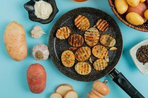 bovenaanzicht van gebakken aardappelschijfjes in koekenpan met ongekookte in mand mayonaise knoflook zout zwarte peper op blauwe achtergrond