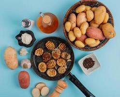 Bovenaanzicht van gebakken aardappelschijfjes in koekenpan met ongekookte in mandje mayonaise knoflook zout zwarte peper en boter op blauwe achtergrond