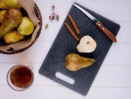 bovenaanzicht van een schijfje peer met kaneelstokjes en keukenmes op een zwarte snijplank een rieten mand met rijpe peren en een glas limonade op witte houten achtergrond