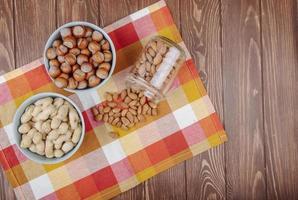 Bovenaanzicht van noten, pinda's, hazelnoten in kommen en amandel verspreid uit een glazen pot op geruite tafelservet op houten achtergrond met kopie ruimte foto