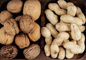 bovenaanzicht van noten, pinda's in de schaal en hele walnoten op houten achtergrond foto