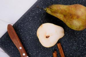 bovenaanzicht van perenplak met kaneelstokjes en keukenmes op een zwarte snijplank op witte houten achtergrond