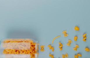Bovenaanzicht van macaronis als farfalle fusilli tagliatelle penne pipe-rigate morsen uit pot op blauwe achtergrond met kopie ruimte foto