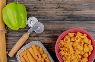 bovenaanzicht van macaronis als ziti en pipe-rigate in kommen met peper op houten achtergrond foto