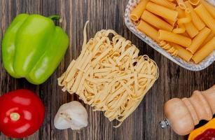 bovenaanzicht van macaronis als tagliatelle ziti met peper knoflook tomaat zout op houten achtergrond foto