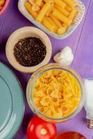 bovenaanzicht van macaronis als penne en anderen met tomaat zwarte peper zout knoflook en plaat op paarse achtergrond