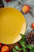 bovenaanzicht van perziken en dennenappel rond lege plaat op doek op houten achtergrond versierd met bladeren