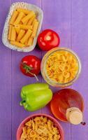 bovenaanzicht van macaronis als penne pipe-rigate en anderen met tomatenpeperboter op paarse achtergrond foto