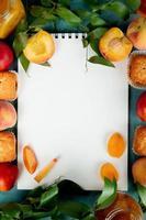 bovenaanzicht van perziken cupcakes perzikjam met notitieblok in het midden op blauwe achtergrond versierd met bladeren met kopie ruimte