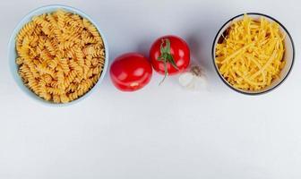 bovenaanzicht van macaronis als rotini en tagliatelle met tomaten en knoflook op witte achtergrond met kopie ruimte