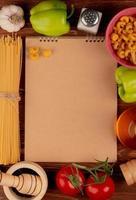 Bovenaanzicht van macaronis als spaghetti en anderen knoflook peper tomaat zwarte peper zout boter rond notitieblok op houten achtergrond met kopie ruimte foto