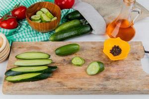 Zijaanzicht van hele gesneden en gesneden komkommers en zwarte peper op snijplank met tomaten gesmolten olie kom met plakjes komkommer en komkommers morsen uit zak op houten achtergrond foto