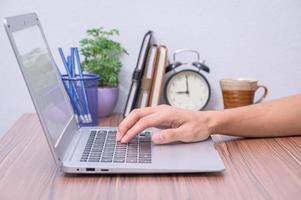 hand van een persoon met behulp van een laptopcomputer foto