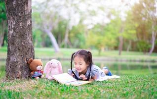 schattig klein meisje dat een boek leest terwijl ze met een pop in het park ligt foto