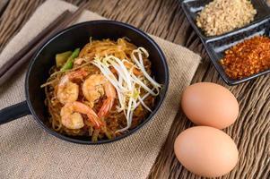pad thai garnalen in een zwarte pan met eieren en kruiden