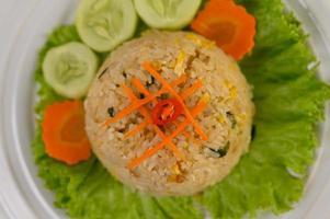 gebakken rijst op een witte plaat met sla en garnituur