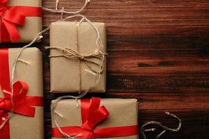 Kerstmis en Nieuwjaar met geschenkdozen en lichtslinger decoratie op houten tafel achtergrond bovenaanzicht met kopie ruimte foto