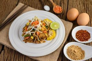 pad thai met citroen, eieren en kruiden op een houten tafel