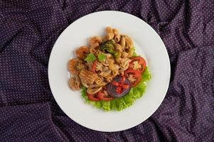 geroerde garnalenmacaroni op een witte plaat met tomaten en salade