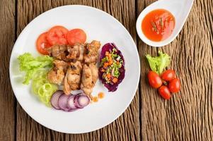 gegrilde kip op een houten snijplank met salade