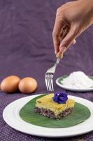 een vork reikt naar een dessert met zwarte kleefrijst