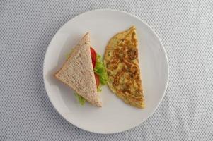 een ei-omelet en sandwich op een witte plaat