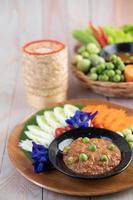 chilipasta in een kom met aubergine, wortelen, chili en komkommers