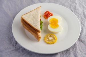 gekookte eieren, maïs, tomatensandwich op een witte plaat