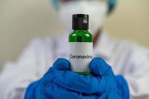 wetenschapper die maskers en handschoenen draagt en covid-19-flesjes bij zich heeft