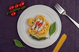 vergulde spaghetti en varkensvlees gerangschikt op een witte plaat