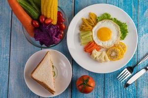 gebakken ei ontbijt met ei, salade, pompoen, komkommer, wortel en mais