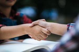 jonge studenten schudden elkaar de hand op schoolpark foto