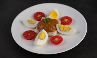 brood gegarneerd met chilipasta met gekookte eieren en tomaten