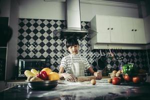 kleine chef-kok die deegroller gebruikt foto
