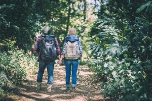 jong koppel wandelen met rugzakken in het bos foto