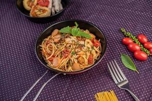 gekruide spaghetti in een koekenpan foto