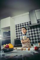 schattige kleine jongen leren koken staande in de keuken foto