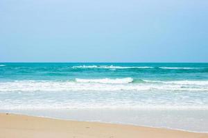 zand en water op het strand met een heldere blauwe hemel