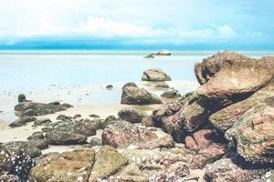 rotsen op strand met bewolkte blauwe hemel