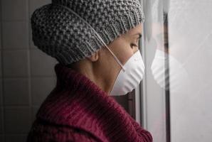 vrouw met gezichtsmasker kijkt uit een raam