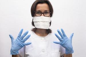 verpleegster die een masker en blauwe handschoenen draagt in het ziekenhuis foto