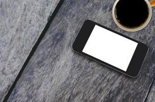 bovenaanzicht mobiele telefoon en koffiekopje