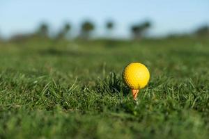 gele golfbal op de grond bij de driving range foto