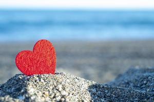 rood hart op een berg zand bij de zee. concept van san valentijn