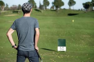 golfer op zijn rug leunend op een golfclub die naar de horizon kijkt foto