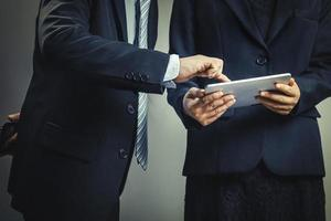 twee mensen uit het bedrijfsleven kijken naar een tablet foto